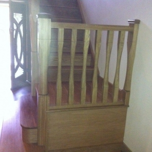 Solid oak, with slender spindles and newels